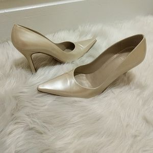 Stuart Weitzman pointed toe gold pumps.